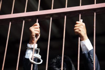 Corporate crime, businessman behind bars, criminal law