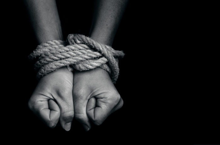 human trafficking, hands tied with rope
