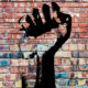 revolutionary fist graffiti on wall representing social justice