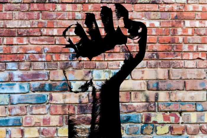 revolutionary fist graffiti on wall representing social justice