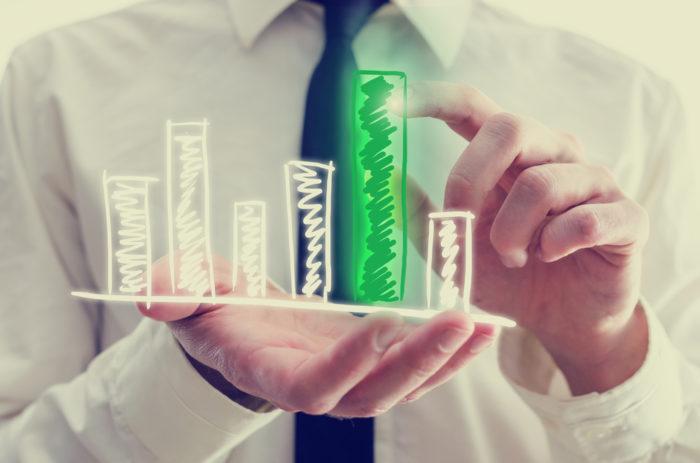 Businessman holding green bar chart