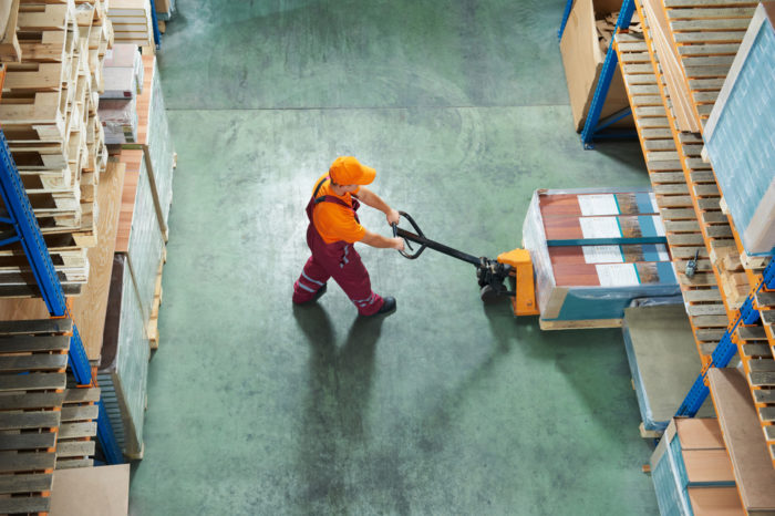 worker in warehouse stacking boxes