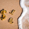 Currency symbols on the sand of tax havens