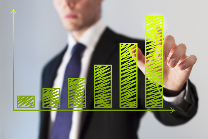 Businessman looks at green graph showing growth