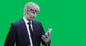 Roman emperor in a suit checks his mobile device