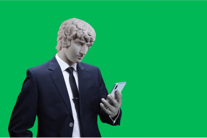 Roman emperor in a suit checks his mobile device