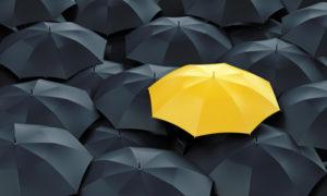 Yellow umbrella in a crowd of black umbrellas