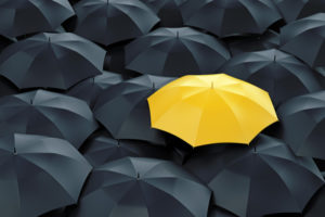 Yellow umbrella in a crowd of black umbrellas