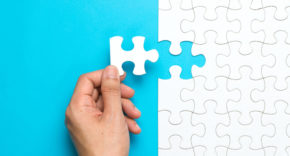 Person placing final piece of jigsaw puzzle