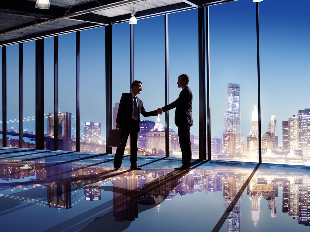 Businessmen shaking hands in from of cityscape