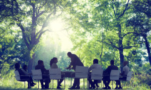 Boardroom meeting on sustainability in a forest