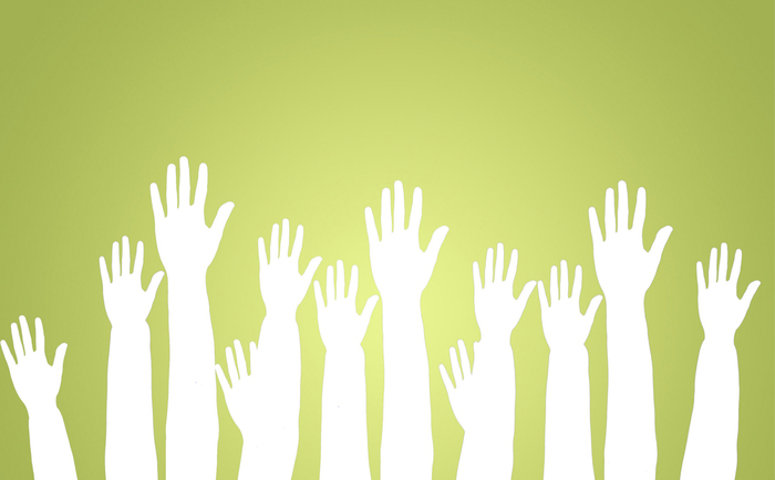 Group of raised hands on green background
