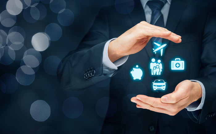Businessman with insurance icons in his hands