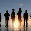 Sun rising behind a group of business people