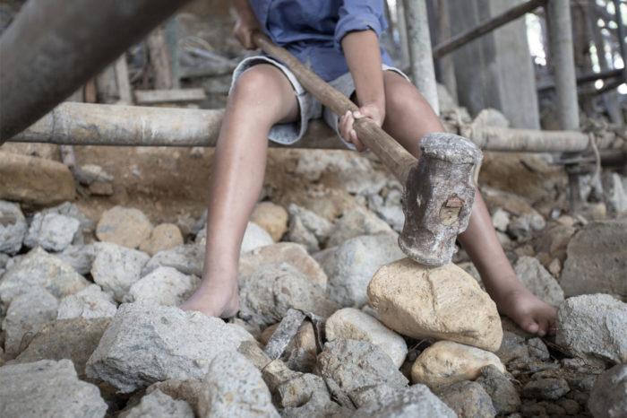 Child labourer breaking rocks