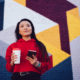 Young Gen Z woman with coffee and phone in front of brightly painted wall